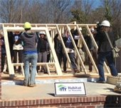 Volunteers raising wall at a Habitat construction site