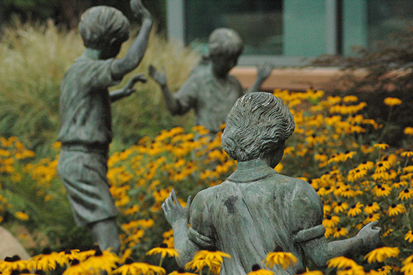 Statue of children playing among fresh flowers